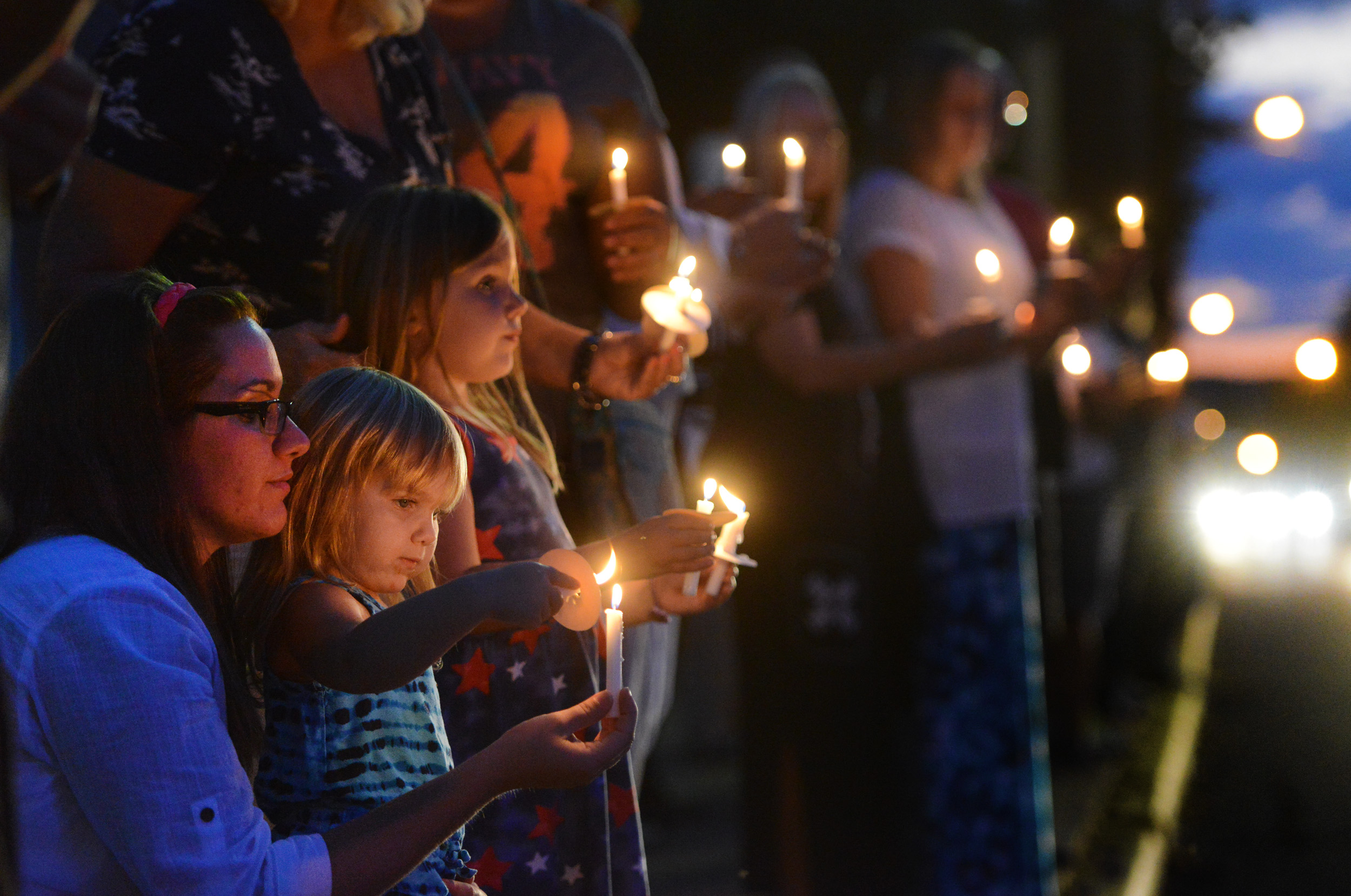 Gretchen Conklin, 2, of Springdale, keeps her flame lit with a candle belonging to her mother, Sarah Moorhead, as her sister Genevieve Conklin looks out towards Pittsburgh Street in Springdale during a candlelight vigil hosted by Springdale Helping Our Peers Everyday on Monday, Aug. 24, 2015.