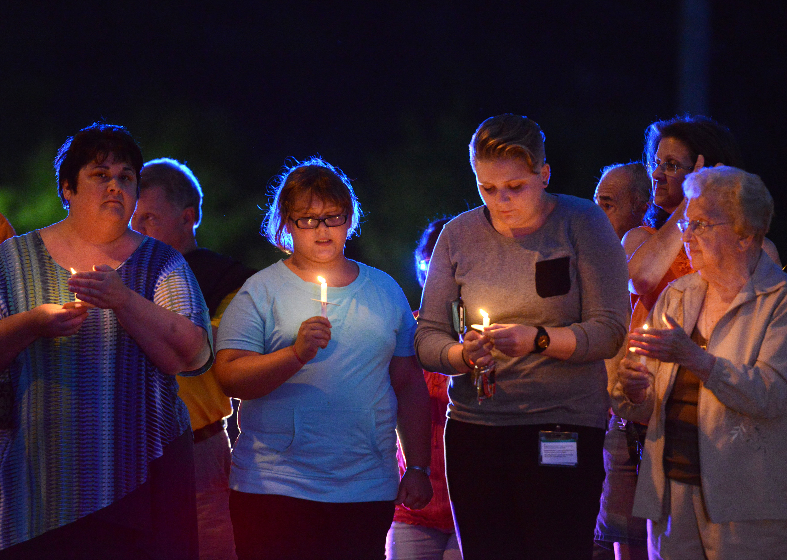 Helayna Baer, 11, of Cheswick, gazes towards her candle with her mother, Denise Baer, and former babysitter Jodi Holmes, 23, of Springdale, who was there with Jodi's grandmother Josephine Funkhouser, of Springdale, while standing along Pittsburgh Street in Springdale during a candlelight vigil hosted by Springdale Helping Our Peers Everyday on Monday, Aug. 24, 2015.