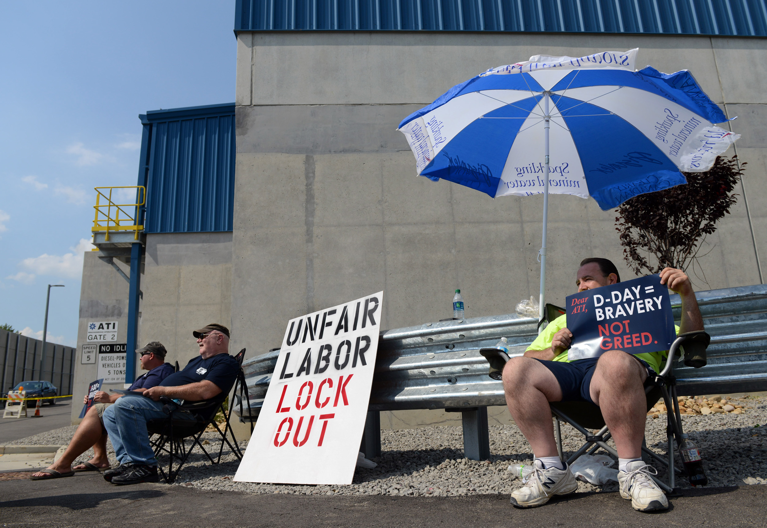 Lenny Rajski, of Lower Burrell, displays his opinion as he tries to stay in the shade of an umbrella while he and fellow ATI workers (center) Jeff Schneider, of Tarentum, and Brad Vakulick, of Springdale, picket in 90 degree heat outside of ATI Allegheny Ludlum in Harrison on Monday, Aug. 17, 2015.