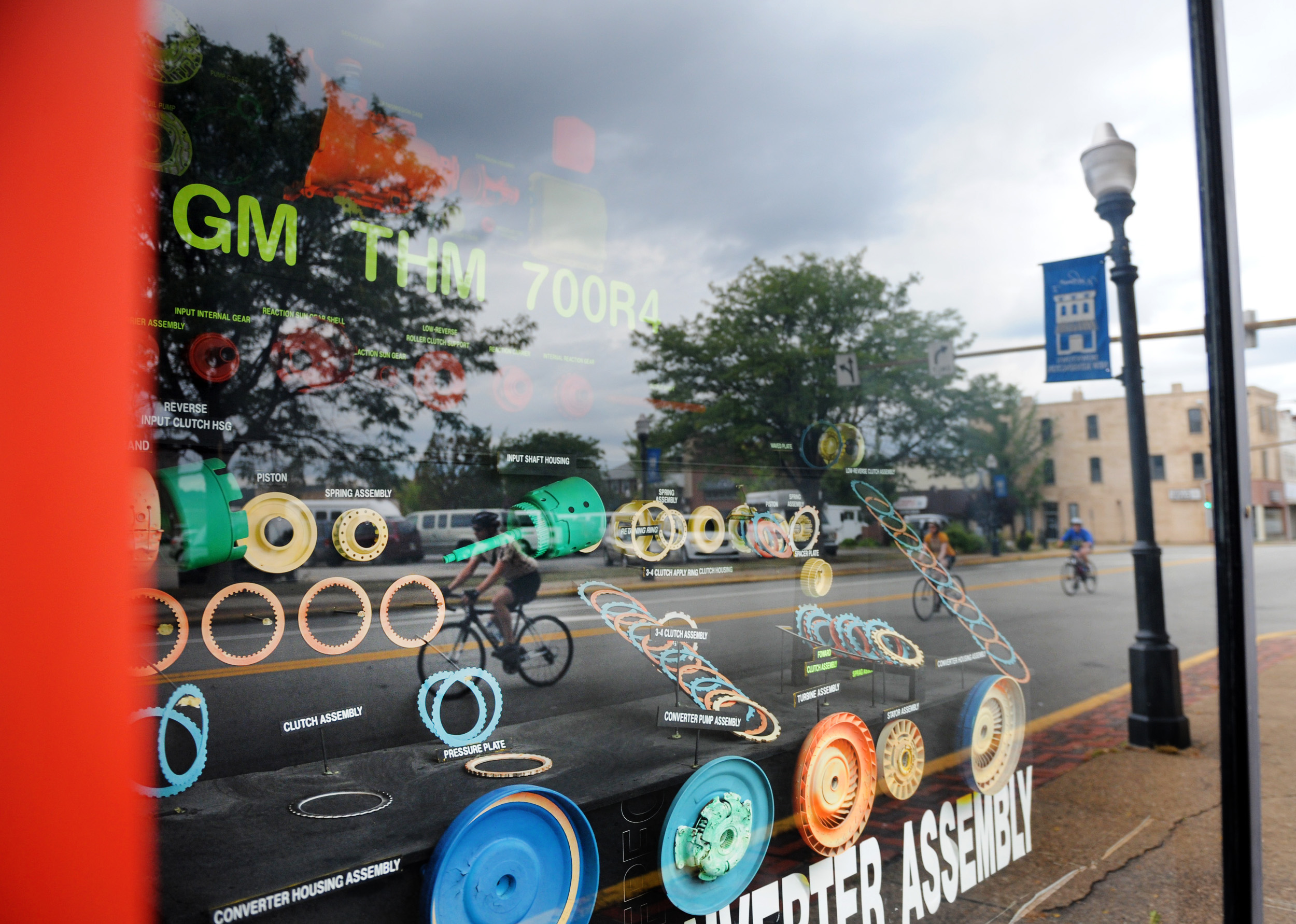 Members of the Allegheny Valley Cyclists are reflected in a window as they travel along 9th Street in New Kensington on Tuesday, Aug. 25, 2015.