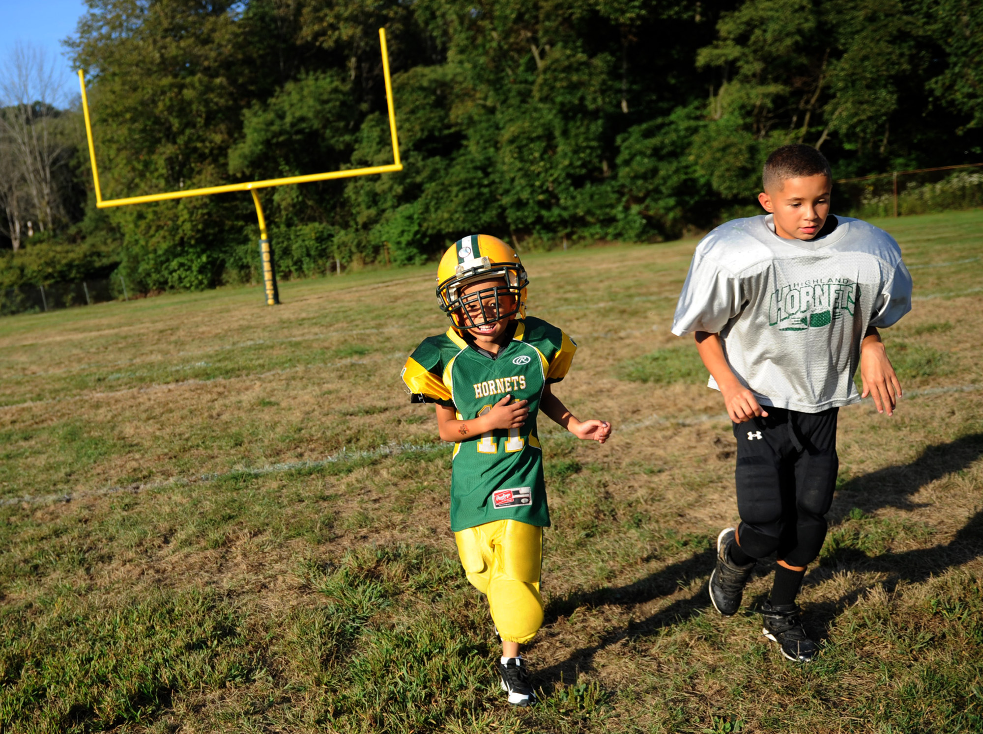 "6-year old Anton ""Tubby"" Clayborn Jr. runs laps with his brother Malik Febbinger during football practice at Bushman Stadium in Harrison Township on Tuesday, Sept. 15, 2015. On Saturday, the Highland Hornets youth football team arranged for Anton to make a touchdown against the Butler Knights. Anton has a rare brain disorder that has required many surgeries and is mostly on the sidelines as he cannot be tackled."