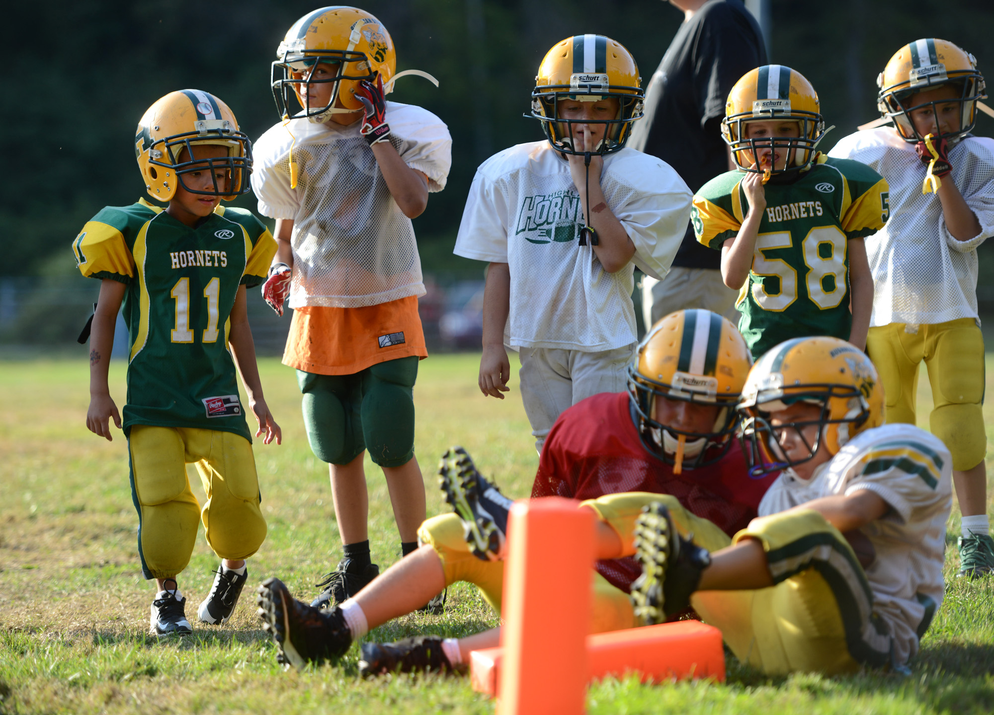 "6-year old Anton ""Tubby"" Clayborn Jr. (11) watches as his teammates stand up after tackling each other--something Anton cannot do--during football practice at Bushman Stadium in Harrison Township on Tuesday, Sept. 15, 2015. On Saturday, the Highland Hornets youth football team arranged for Anton to make a touchdown against the Butler Knights. Anton has a rare brain disorder that has required many surgeries and is mostly on the sidelines as he cannot be tackled."
