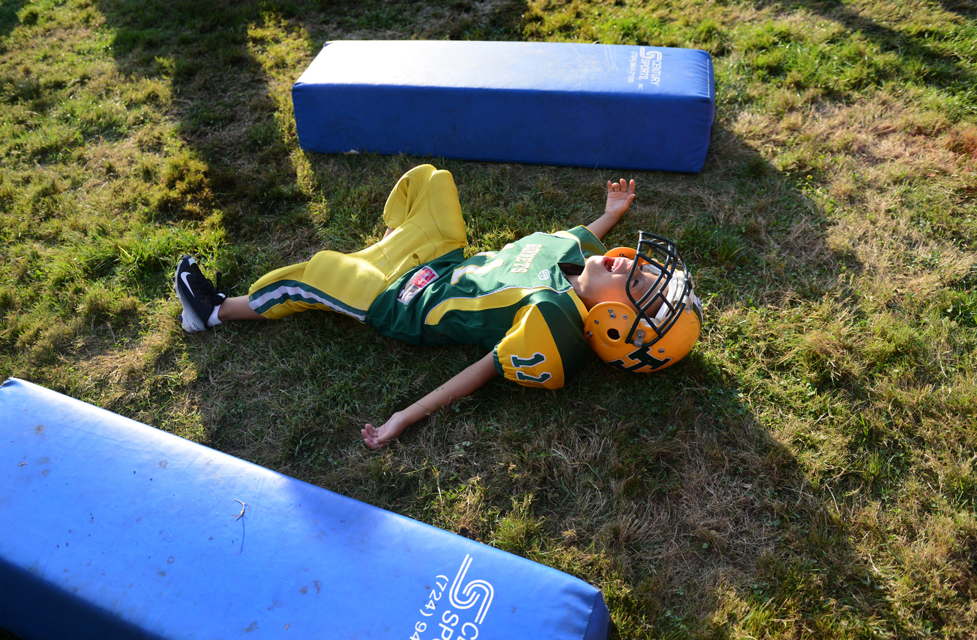 "6-year old Anton ""Tubby"" Clayborn Jr. (11) laughs as he rolls on the ground after falling from tackling a teammate with extra enthusiasm during football practice at Bushman Stadium in Harrison Township on Tuesday, Sept. 15, 2015. On Saturday, the Highland Hornets youth football team arranged for Anton to make a touchdown against the Butler Knights. Anton has a rare brain disorder that has required many surgeries and is mostly on the sidelines as he cannot be tackled."