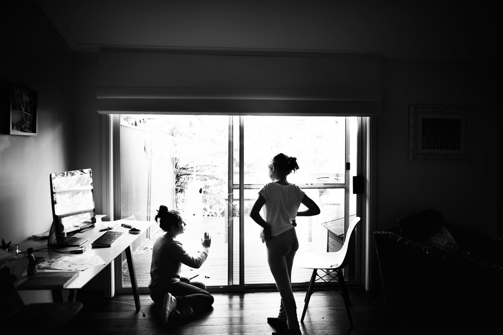 sisters drawing on a window. lifestyle family photography in Sydney