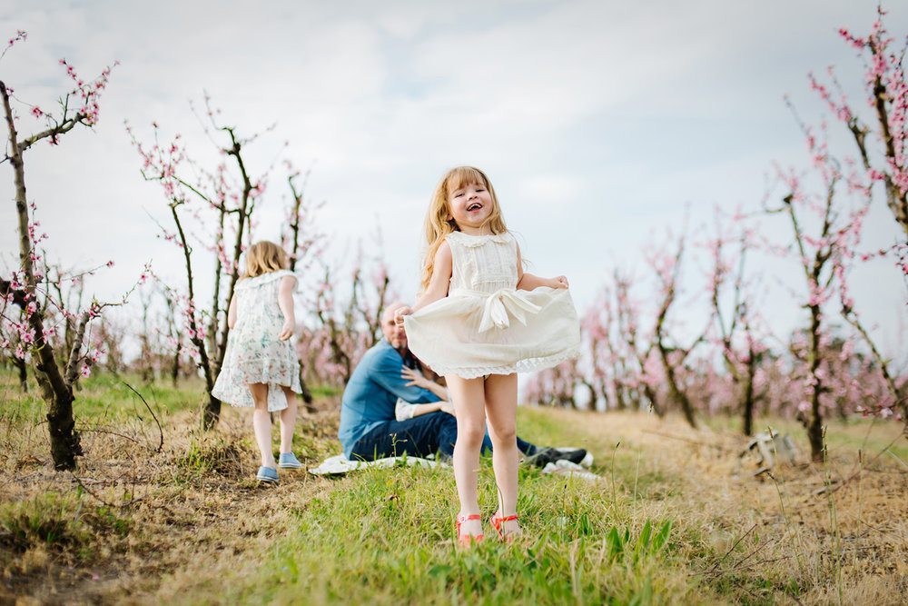 Lifestyle portraits captured by Cindy Cavanagh in a spring orchard