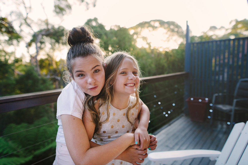 Sisters playing as the sunsets on a verandah by Sydney photographer, Cindy Cavanagh.