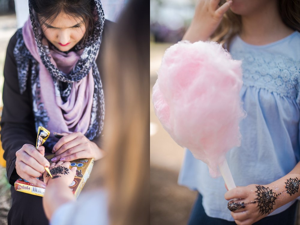 A girl eating fairy floss and getting her hand painted with henna in Castle Hill by lifestyle photographer, Cindy Cavanagh