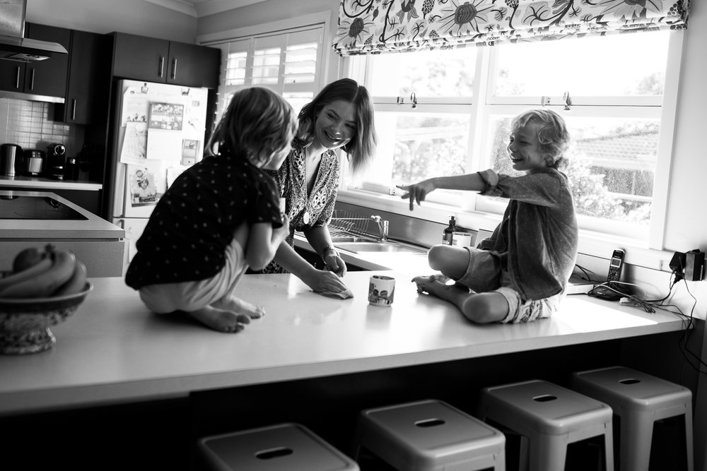 A Lifestyle portrait session in your home is a great way to document the fun moments, like making Milo and laughing with your family. Captured by Cindy Cavanagh, Sydney Photographer.