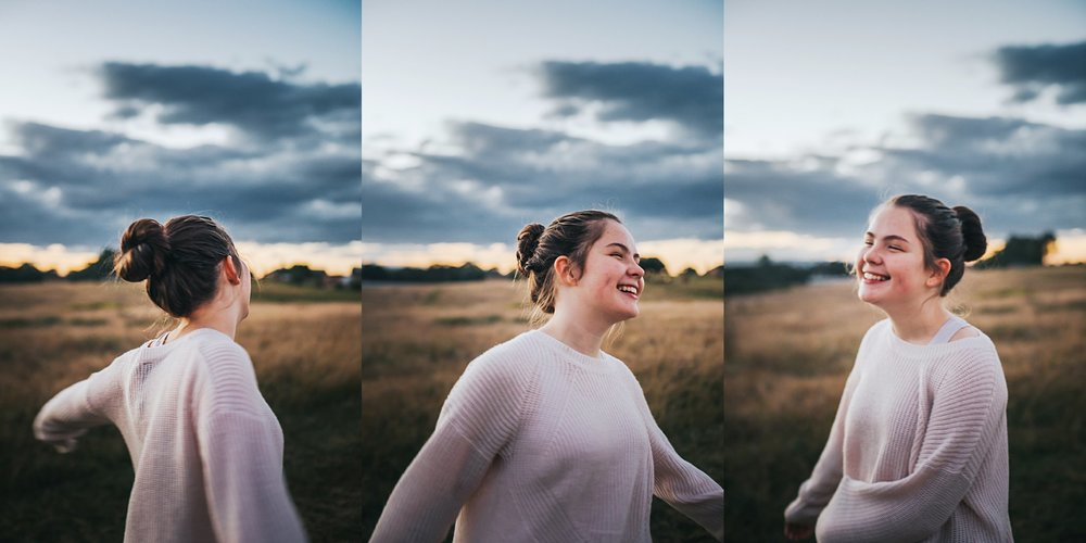 A lifestyle portrait of a teenage girl spinning in a field of long grass at sunset in Rouse Hill, Sydney.