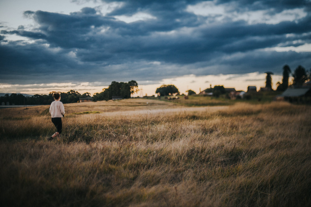 A lifestyle portrait of teenage girl walks through a field of long grass as the sun sets on a cloudy day in Rouse Hill, Sydney