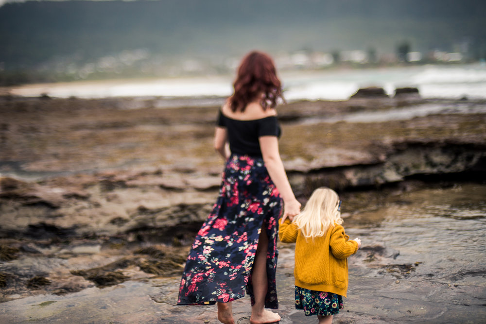 A beach portrait captured during a motherhood session in Sydney as Mum and daughter walk on the rocks, holding hands, and being in the moment.