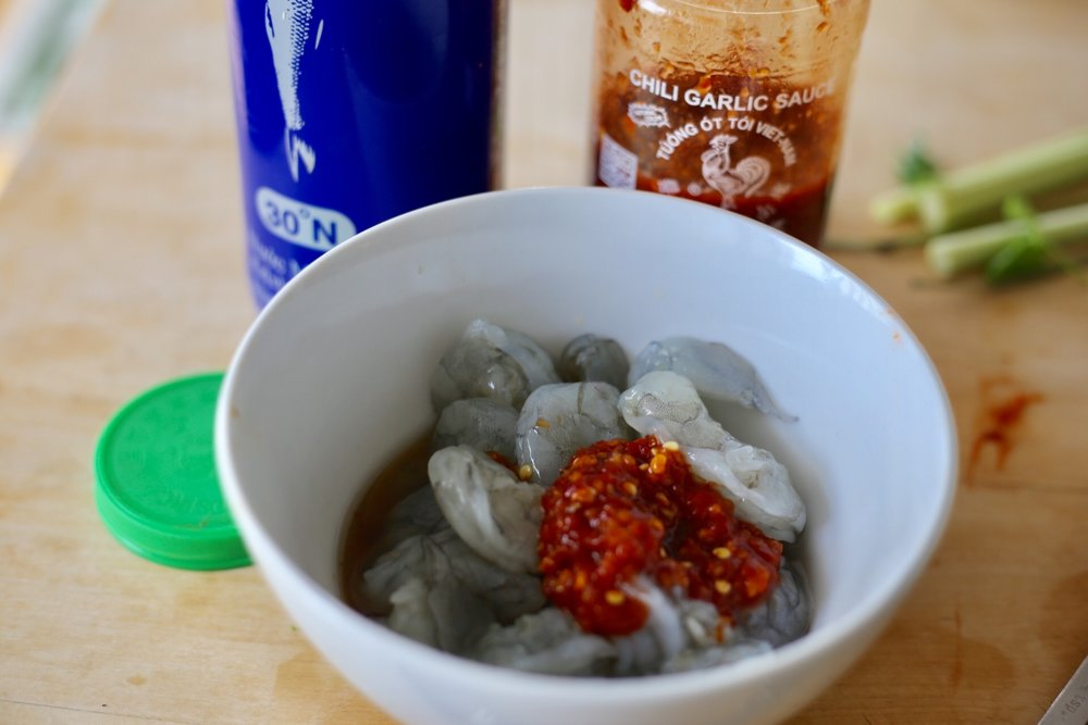 Marinate peeled and deveined shrimp in 1 tablespoon each chili garlic sauce and fish sauce