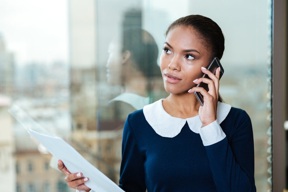 graphicstock-afro-business-woman-in-dress-talking-on-phone-and-standing-near-the-window-in-office_rIMgZ8v7_ng.jpg