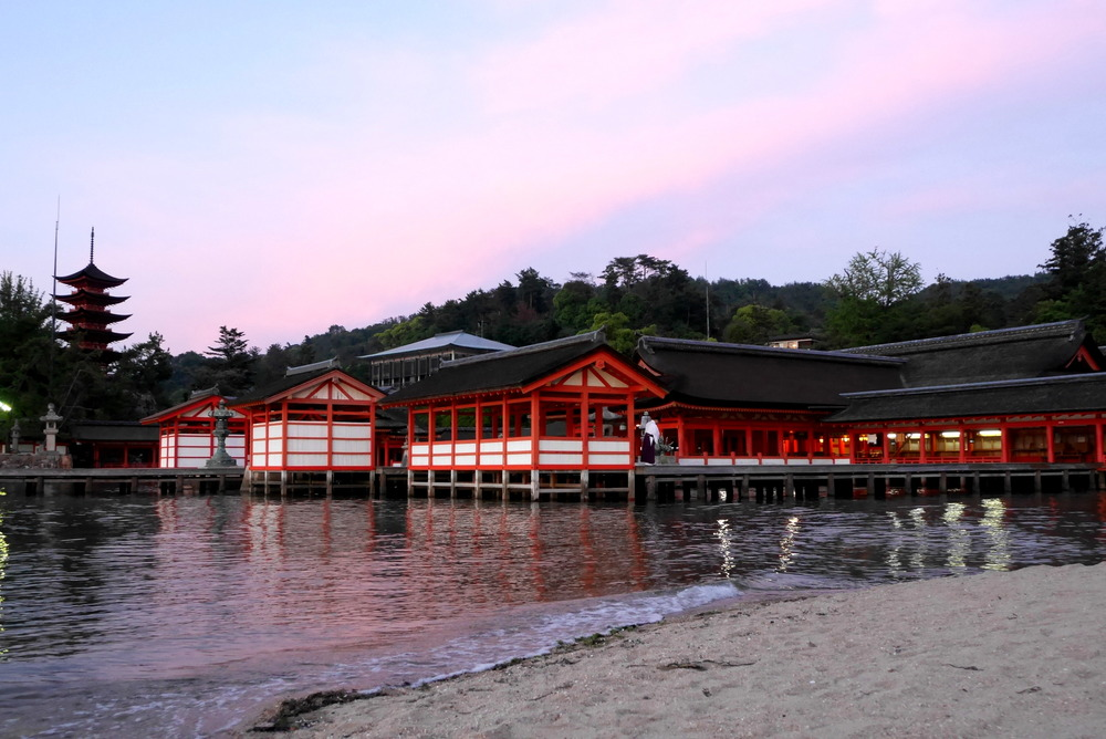 A priest sweeps at Itsukushima Shrine at sunset