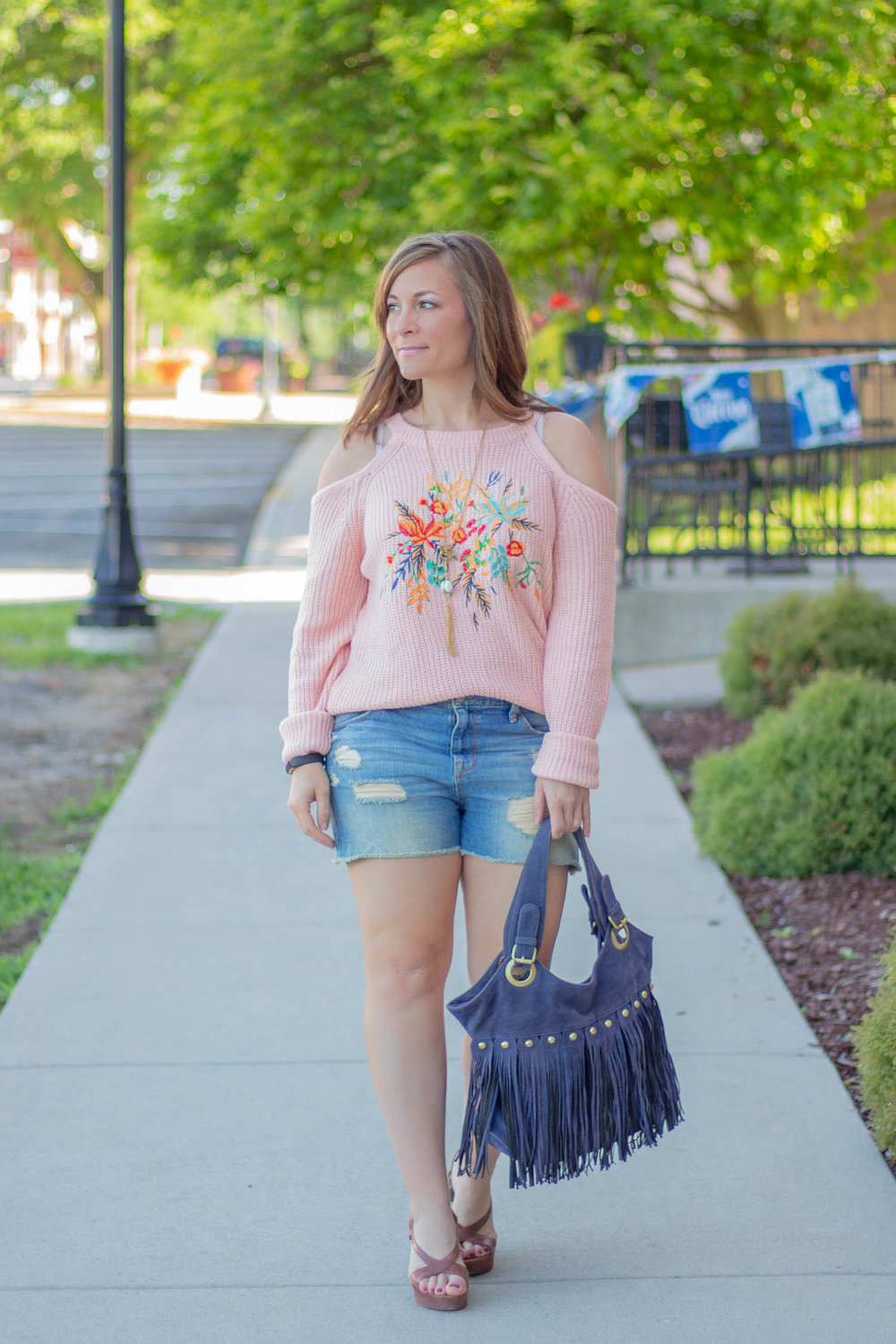 A perfectly cute outfit for summer, especially on cool night, is a cold shoulder sweater with embroidery and cutoffs. Add strappy wedge sandals and viola, summer perfection!