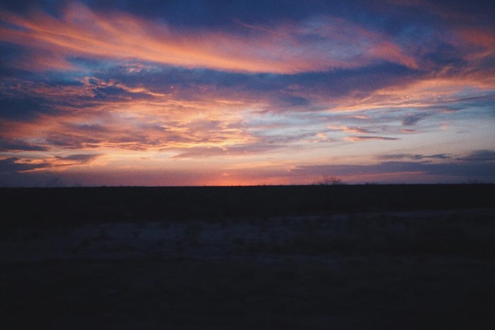운전하면서 보이는 지평선 위에 석양. The sunset I see on the horizon while driving.