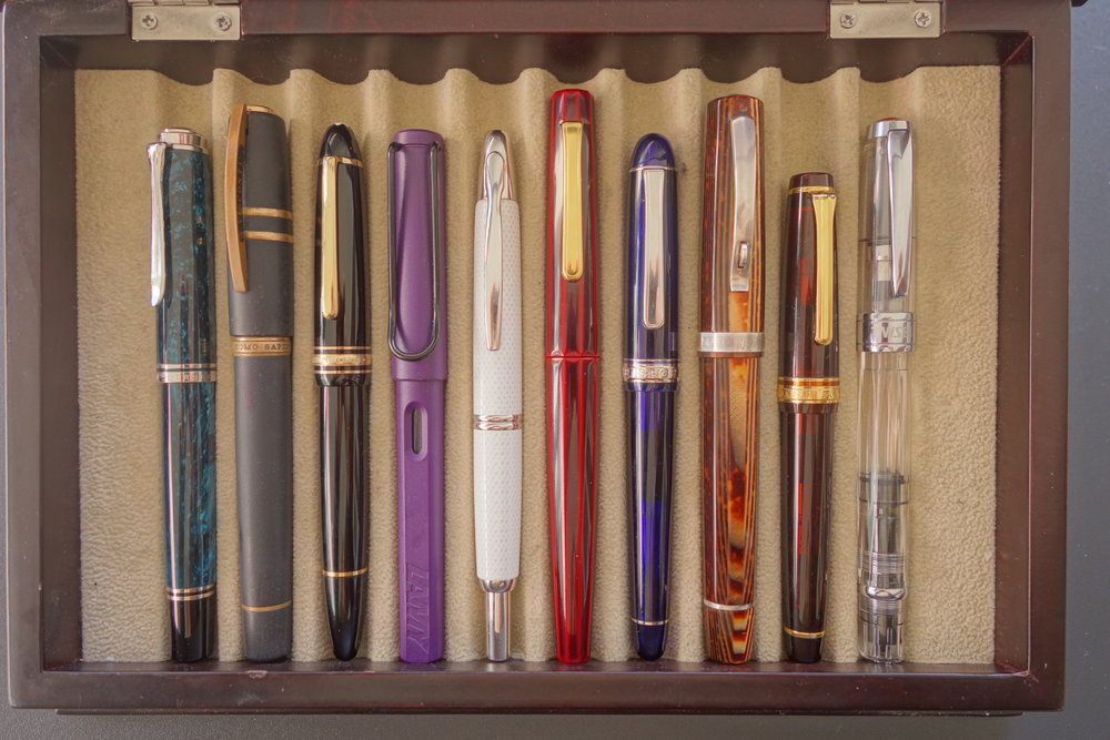 "Left to right: Pelikan M805 ""Ocean Swirl"", Visconti Homo sapiens ""Bronze Age"", Montblanc 146, Lamy Safari ""Dark Lilac"", Pilot Vanishing Point ""White Carbonesque"", Nakaya Decapod Writer ""Aka-tamenuri"", Platinum Century #3776 ""Chartres Blue"", OMAS Paragon Arte Italiana ""Arco Brown"", Sailor Pro Gear (Wancher exclusive) ""Mocha"", and TWSBI Diamond 580."