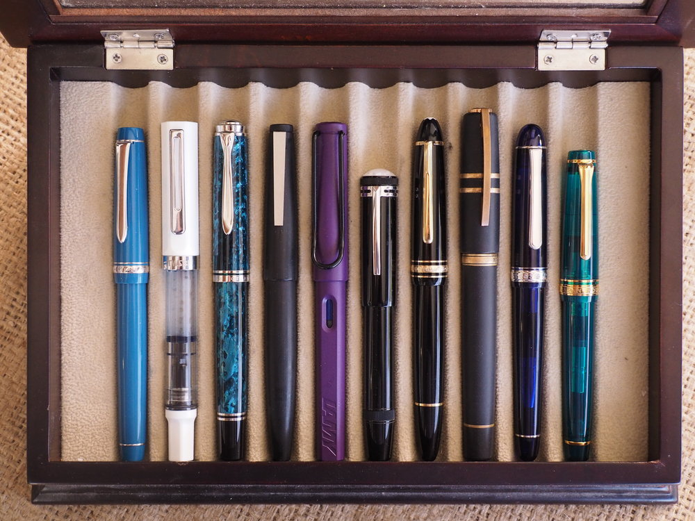 Left to right: Pilot Custom 91 (Tsuki-yo), TWSBI Eco (white), Pelikan M805 (Ocean Swirl), Lamy 2000, Lamy Safari (Dark Lilac), Montblanc Heritage 1912, Montblanc Le Grand 146, Visconti Homo Sapiens (Bronze Age), Platinum Century #3776 (Rhodium Chartres Blue), and Sailor Pro Gear (Wancher Maldives).
