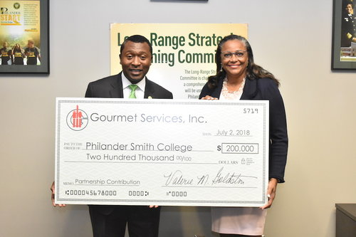 Photo of two people holding a large check.