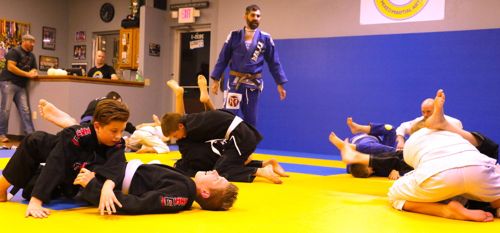 Our 8-15 year olds warming up with armbars and triangles, 2 of our most basic submissions that we try and master through repetition.