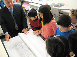 Michael Macaluso with Architots children in his office showing blueprints of a new building.