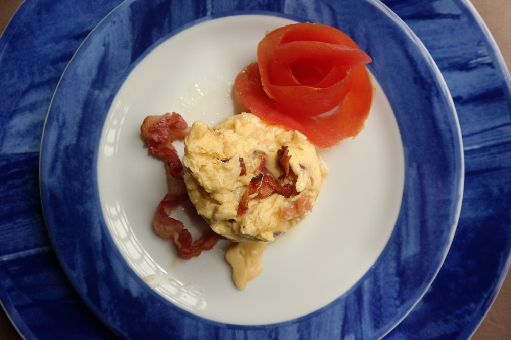 A breakfast of scrambled eggs, bacon, and cheese (with a tomato rose that's almost too pretty to eat!)