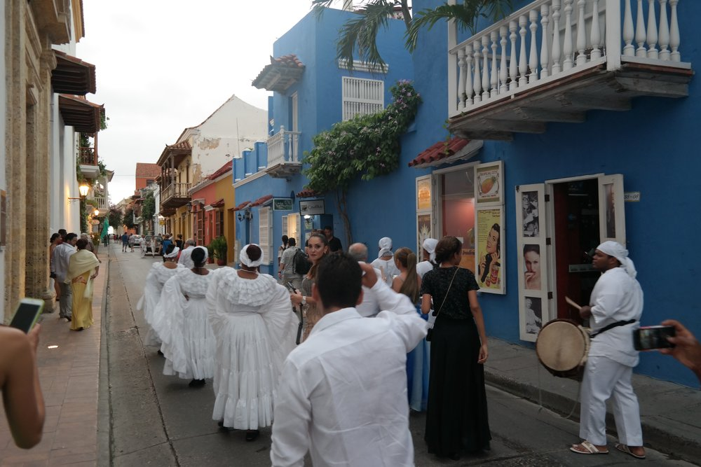 Cumbia dancers and drummers lead the procession down the streets of Old Town Cartagena.