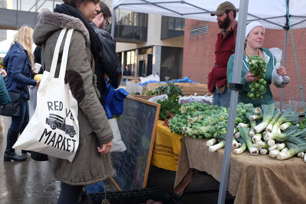 Vendors and patrons interact at the Red River Market.