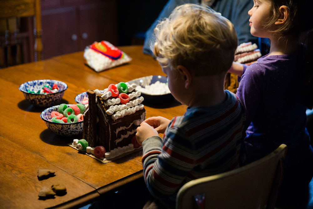 A little boy decorates his gingerbread house during a family storytelling photo session