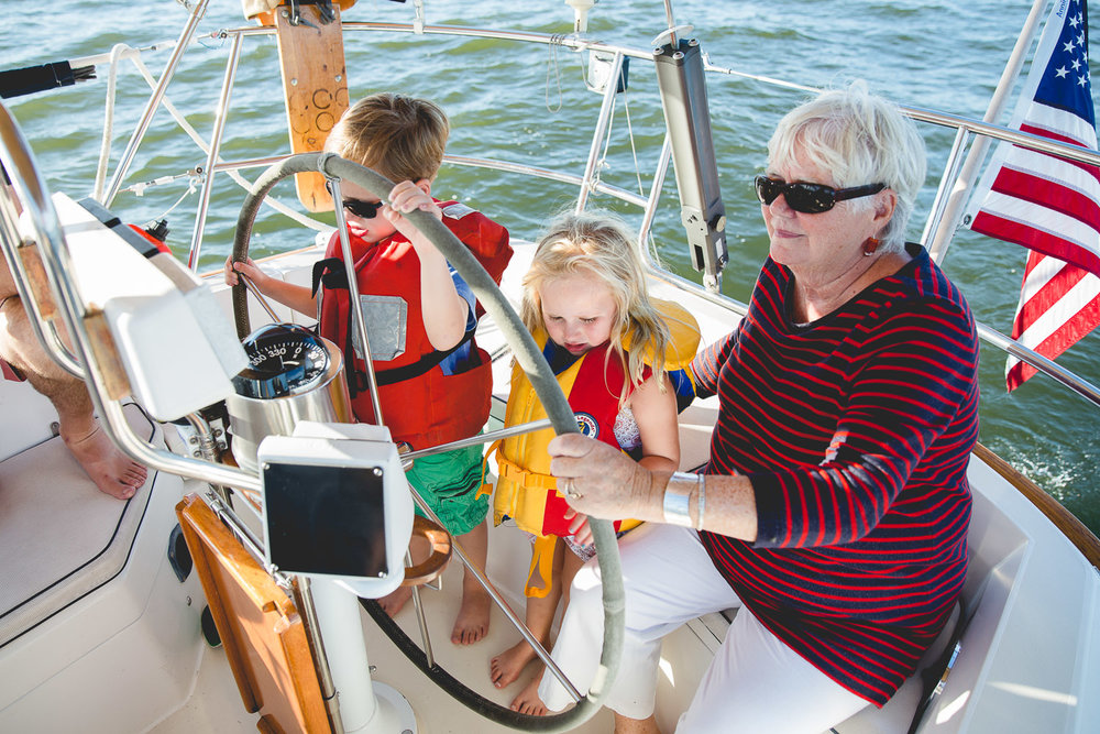 Grandmother steering sailboat with grandchildren on the Chesapeake Bay.