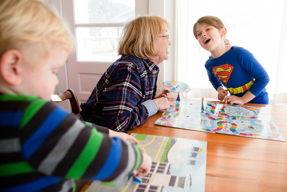Grandmom plays board games with her granddaughter and grandson.