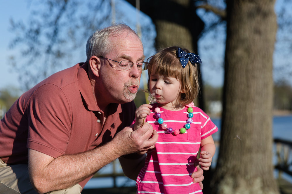 Grandfather blows on a dandelion with his granddaughter during their family storytelling photo session in Annapolis Maryland.