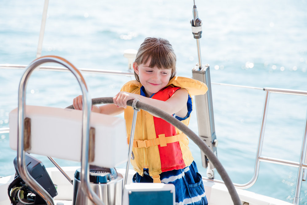 Little girl steering her grandfather's sailboat