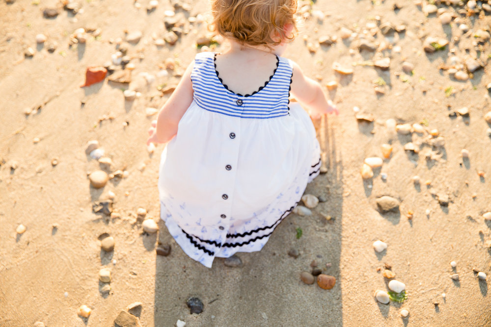 Child looking for seashells on a beach