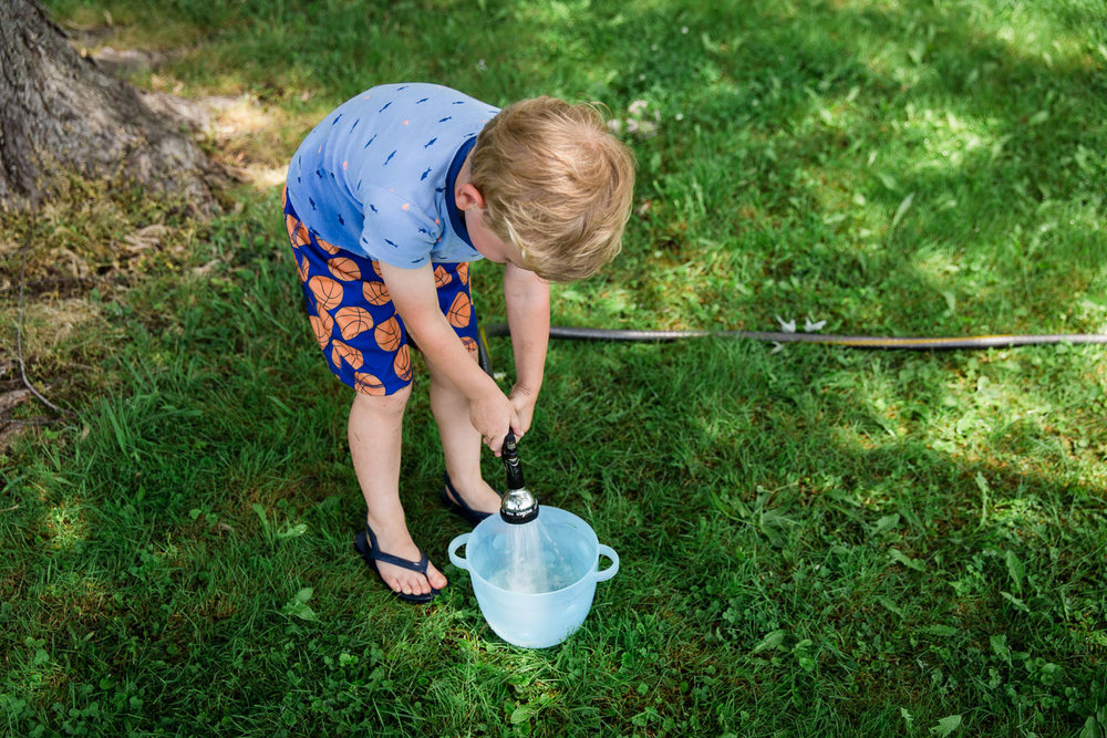 Little boy filling bucket of water in his pajamas
