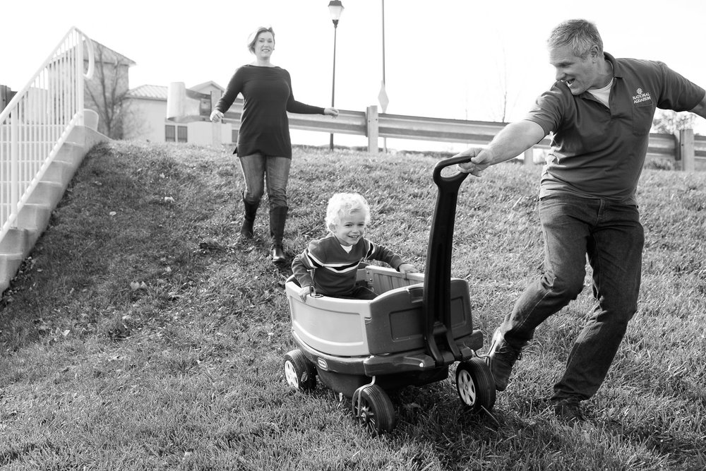 A father pulls his son down a hill in a wagon