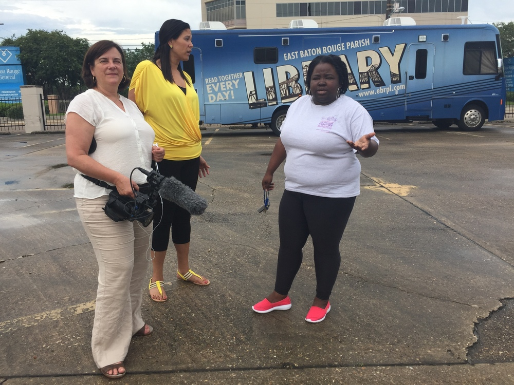 (Left to right) Free for All Director Dawn Logsdon films with Chaundra Johnson and Tameka Roby of the East Baton Rouge Library outreach team in front of their bookmobile. (August 21, 2016)