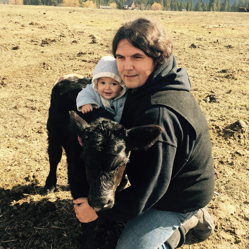 Kale Thomas with his son and a calf