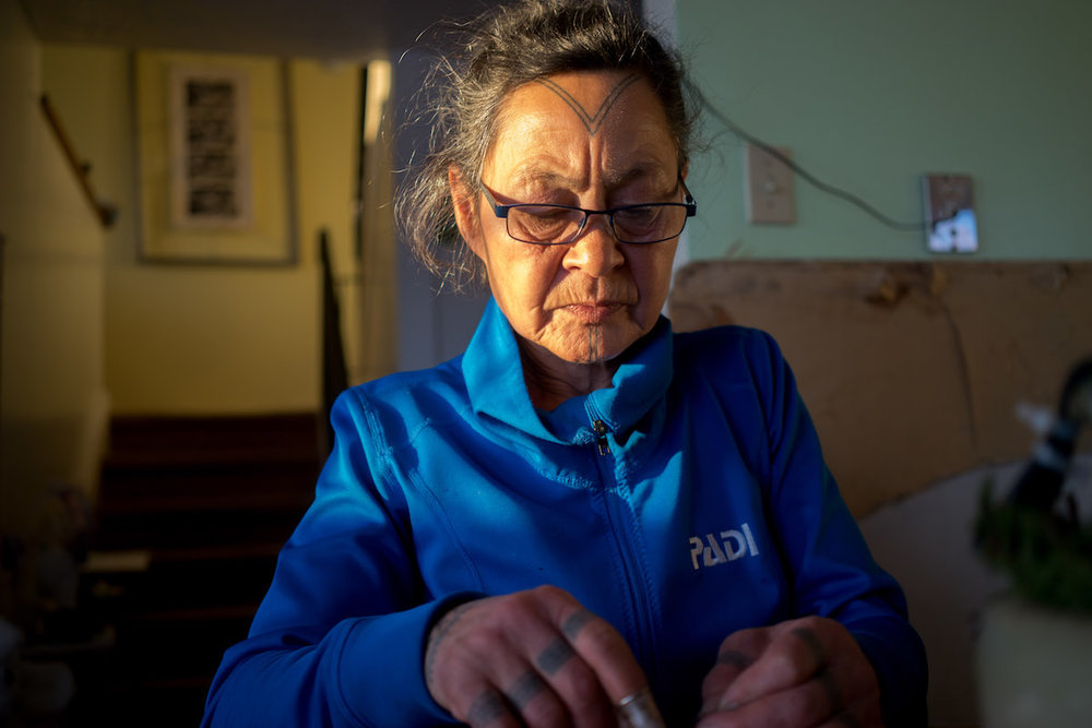 Aaju Peter sews a tie out of sealskin in her home.
