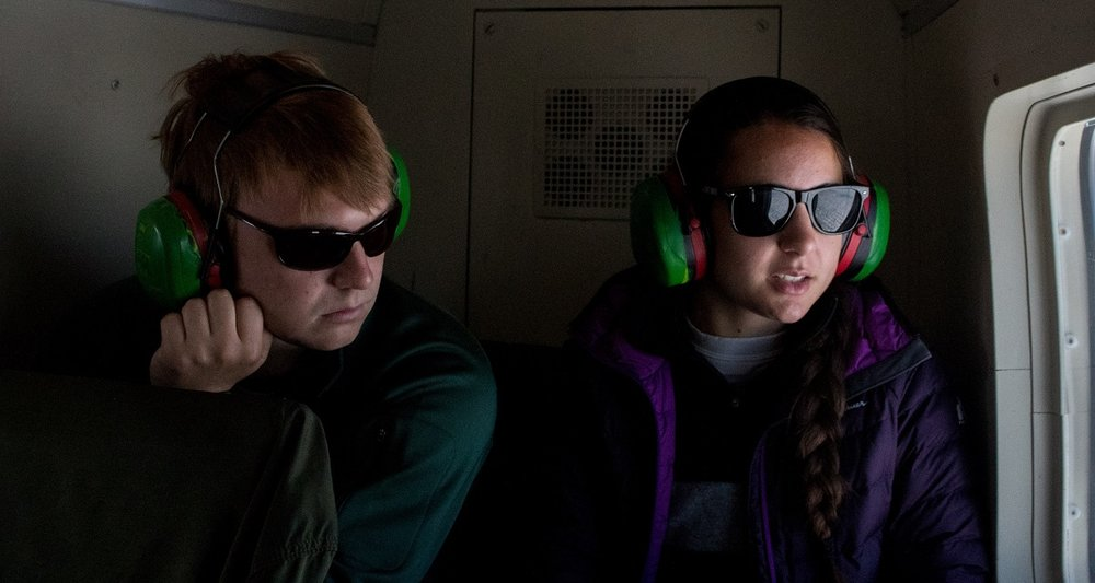 Graduate students Ian MacDowell and Rosie Leone look down on the ice sheet from inside the helicopter.