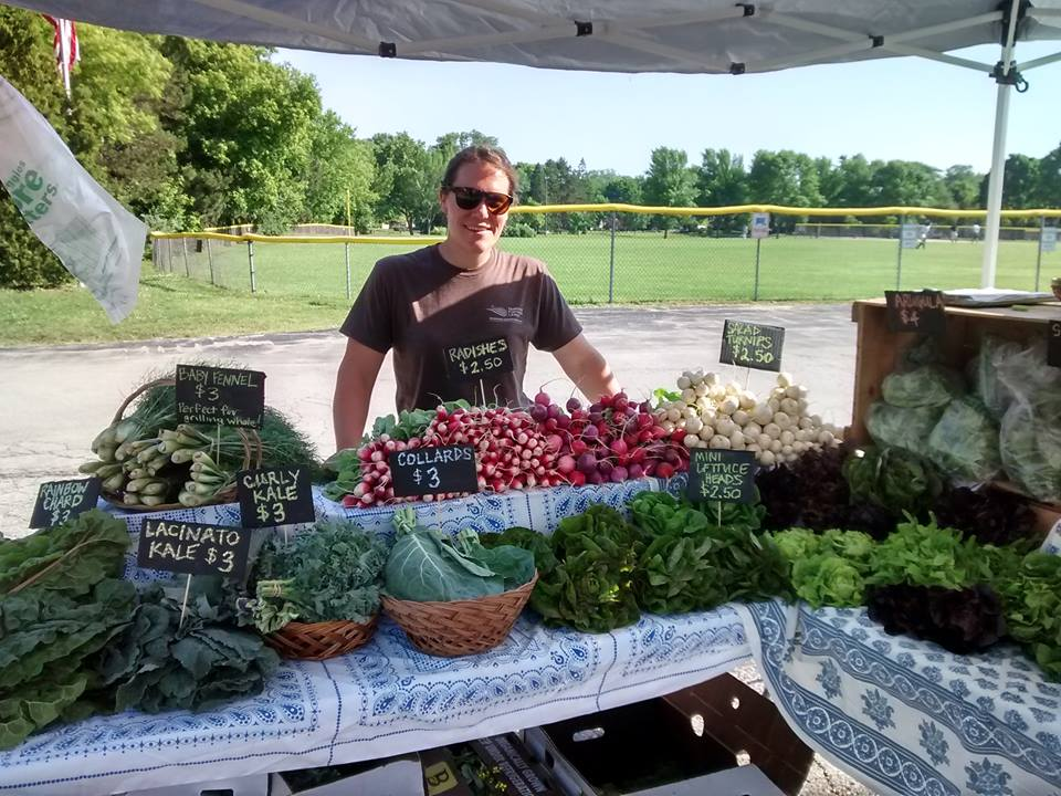 Amy' at her stand at the farmer's market. You can tell it's early in the season because greens are the first things that are ready to harvest.  Photo from Amy's Acre Facebook page.
