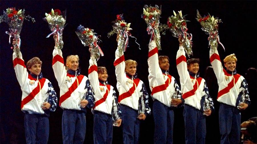 "The ""Magnificent Seven"" US Women's Gymnastics team at the 1996 summer games. From left, Kerry Strug, Jaycie Phelps, Dominique Moceanu, Shannon Miller, Dominique Dawes, Amy Chow, and Amanda Borden (Image via NBC)"