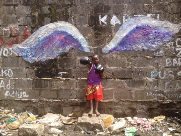 A boy in boxing gloves in front of the Koyale angel wings in Nairobi, Kenya