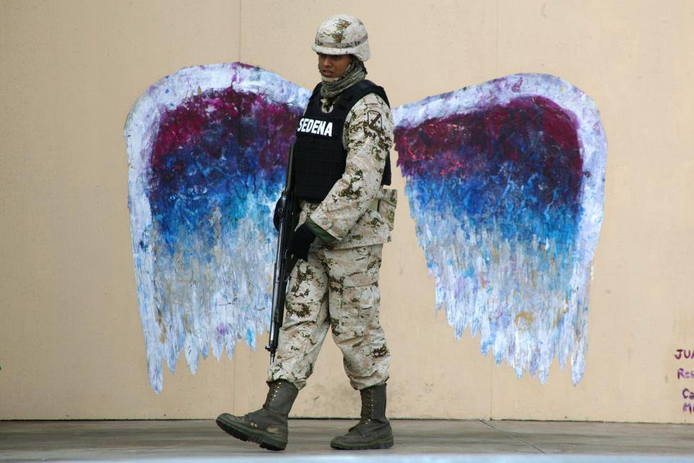 A soldier in front of Colette's angel wings in Juarez, Mexico. This photo appeared in Reuters, the New York Times, and other news services.