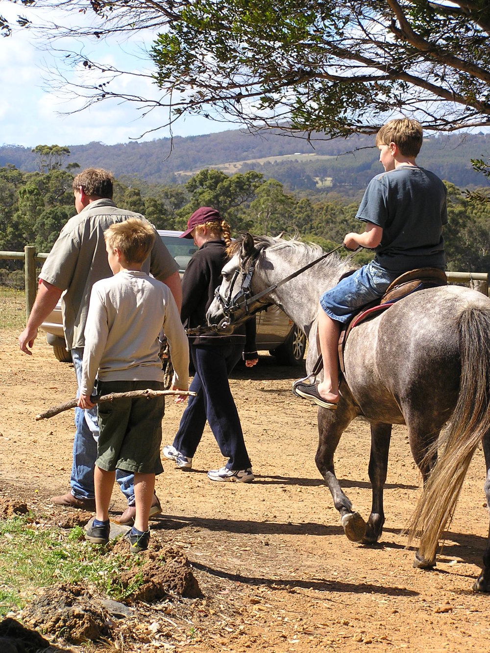 Warren leading a pony ride with three children
