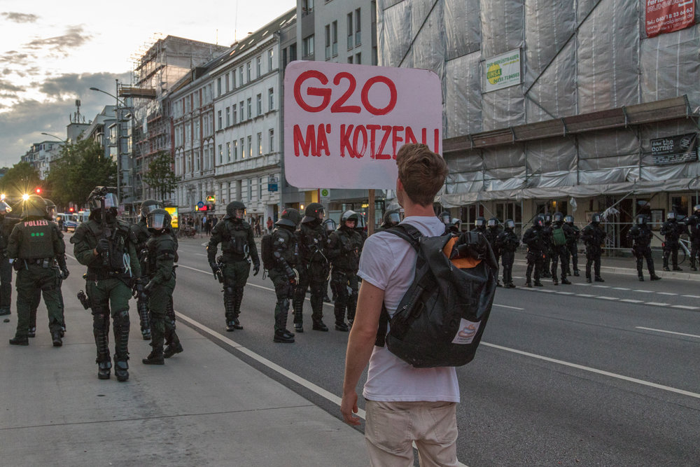 Demonstrant mit Schild vor Polizeikette.jpg