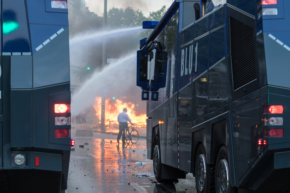 Wasserwerfer vor brennender Barrikade und Mann mit Fahrrad.jpg