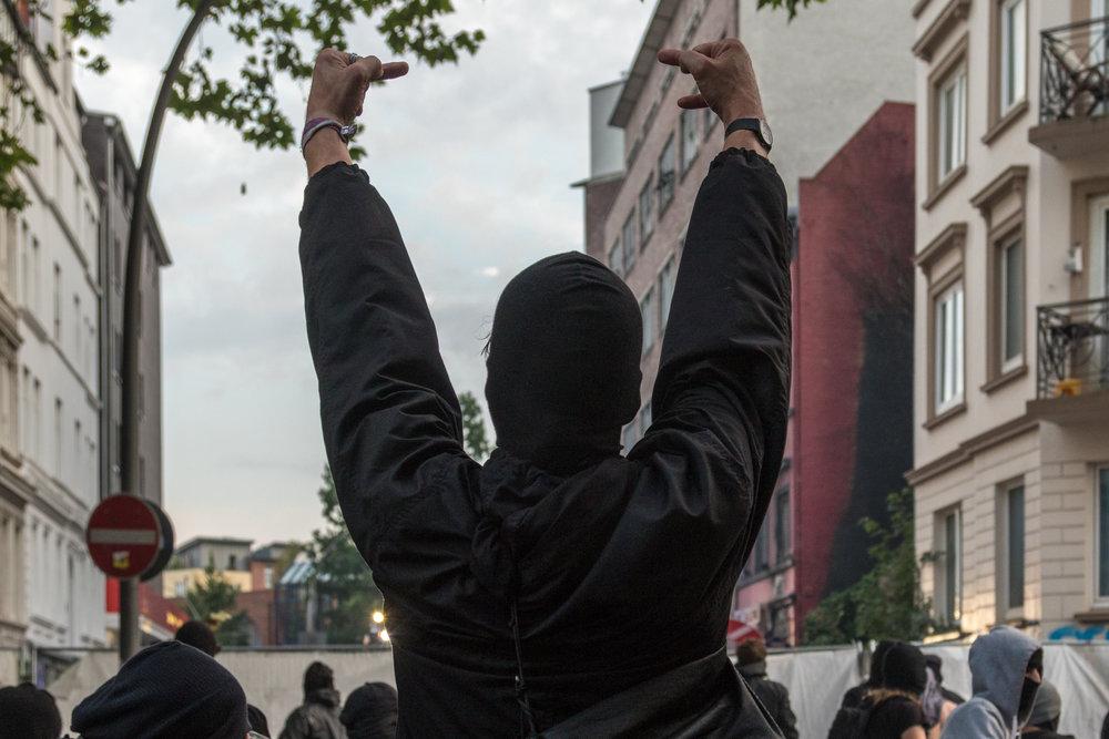 Vermummter zeigt Mittelfinger in Richtung Polizei.jpg