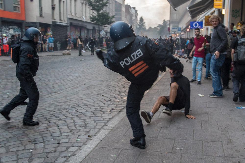 Polizist tritt Mann am Boden.jpg