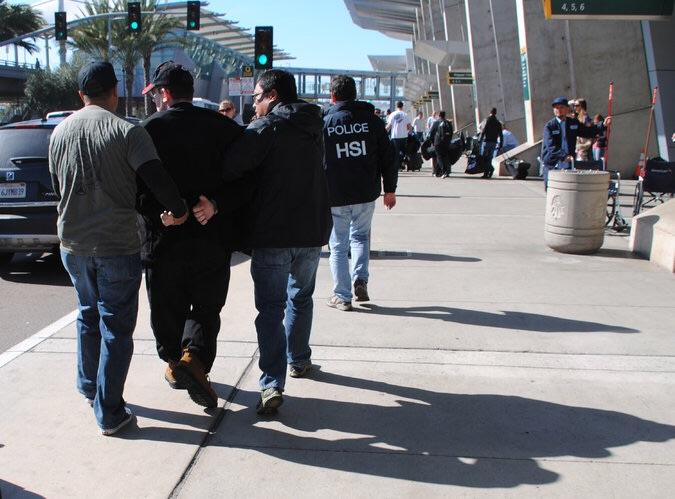 Joel A.Wright, second from left, was arrested at the San Diego airport on Friday. Credit: U.S. Immigration and Customs Enforcement, via Associated Press